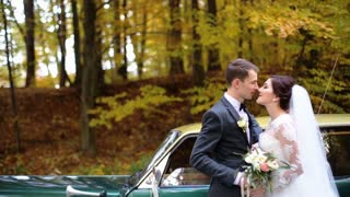 Beautiful just married couple kissing each others in front of a green retro car on the park.