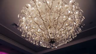 Beautiful retro luxury crystal strass chandelier isolated on a white wall of the restaurant.