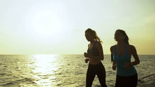 Beautiful scenery of two beautiful female joggers pursuing their activity outdoors in the beach.