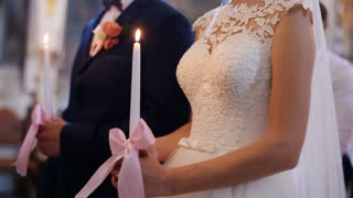 Beautiful sensual blonde bride in white veil and crown and handsome groom, holding candle closeup. Wedding ceremony in church
