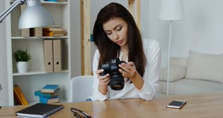 Beautiful smiling brunette photo editor in white shirt looking at a digital camera in her office