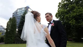 Beautiful stylish newlywed couple posing with pink bridal bouquet in botanic garden, glass structure background