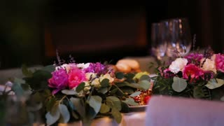 Beautiful wedding decoration made of flowers of different kinds and colors on a wedding table in a fancy restaurant.