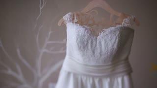 Beautiful white luxury wedding dress on hanger on the background of light interior