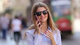 Beautiful woman is looking for her cell phone in her stylish bag. She is wearing classical clothes and her lip is red and adorable