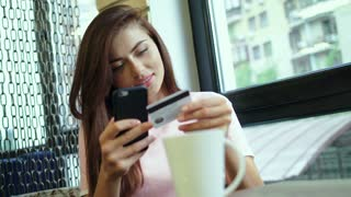 Beautiful woman online banking using smartphone shopping online with credit card
