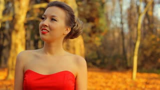 Beautiful woman wearing red dress and with professional make up walk on the park.