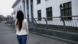 Beautiful woman with long dark hair walking on city street wearing jeans and white jacket