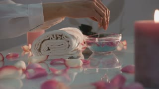 Beautiful woman's hands with perfect french manicure in bowl of water decorated with chrysanthemum flowers