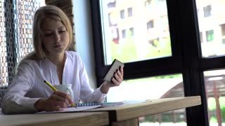 Beautiful young blonde girl inwhite shirt using tablet and making notes, while working in cafe