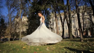 Beautiful young bride in white wedding dress spinning around. Happy bride celebrating her marriage. Slow motion video footage.