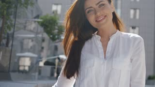 Beautiful young brunette girl posing in a city sunny summer day, in white shirt with blowing long hair