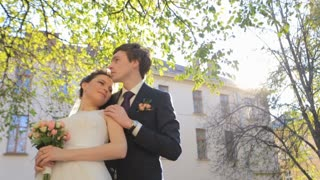 beautiful young couple bride and groom standing in the park and hugging each other shot in slow motion  close up