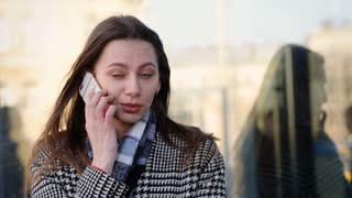 Beautiful young lady talking on phone with her friend and smiling, outdoors.