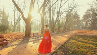 Beautiful young lady wearing amazing red dress walk on the park in autumn .