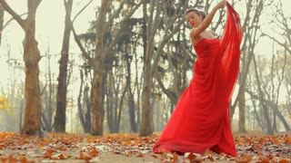 Beautiful young model wearing long evening red dress professionally pose on a camera.