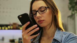 Beautiful young woman in glasses using smartphone, texting messages in cafe