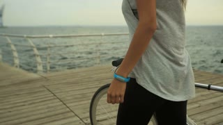 Beautiful young woman with dark color of hair riding a bicycle near the sea on wooden boardwalk.