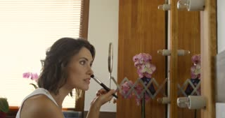 Beauty woman applying makeup at morning. Beautiful girl looking in the mirror and applying cosmetic with a big brush, while her husband standing near