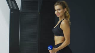 Body and mind workout in loft fitness studio. Closeup on fitness woman holding dumbbell in urban gym