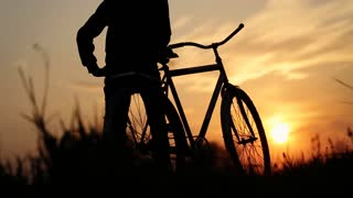 Boy holding his bicycle and watching the sundown.