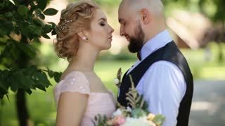 Bride and groom embracing tenderly kissing in a green park, smile and happiness on their faces