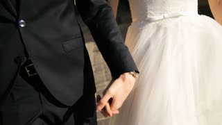Bride and groom walk holding hand in hand. Close-up shot in slow motion