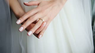 Bride in a beautiful white dress, hands with a wedding ring with a jewel close-up. Morning of the bride. Wedding day.