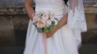 Bride in lace dress holding beautiful white wedding flowers bouquet, close-up