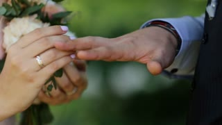 Bride putting wedding ring on groom's finger. Young couple at wedding ceremony. Wedding rings exchange