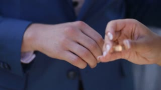 Bride's hand puts gold ring on the finger of groom's hands, blue jacket tuxedo, manicure, wedding ceremony on a sunny day