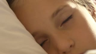 Calm little blonde girl trying to to fall asleep in the bed close-up