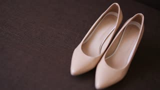 Camera slowly is moving to shoot a pair of classical beige woman's shoes. A concept of Wedding shoes.