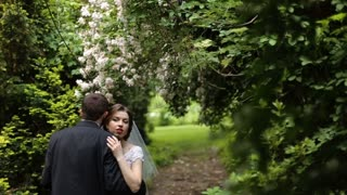 Charming bride and groom hugging in the blossoming spring garden, man standing from the back to the camera