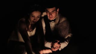 Charming wedding couple sitting in front of campfire warming hands at night, close-up