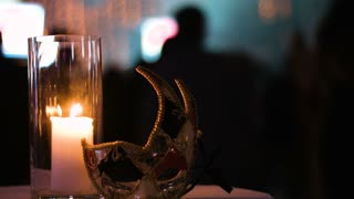 Close-up footage of a firing candle in glass cup and a carnival mask left on a table in a club, people dancing on a background.