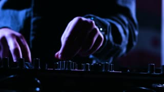 Close-up footage of a male DJs hands mixing music at a party by using his control desk,artist is using his instrument for playing music at a stage.