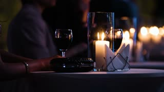 Close-up footage of elegantly decorated table at restaurant,female visitor holding a glass of red wine, fancy black clutch bag is near.
