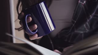 Close-up footage of young female hands hold an opened book and a cup with hot drink.