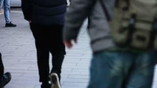 Close-up legs of pedestrians on sidewalk walking through street in winter