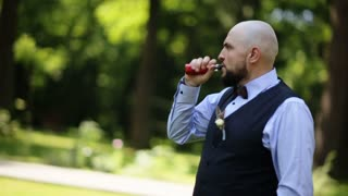 Close-up of a bearded man in suit smoking electronic cigarette, exhale smoke outdoors