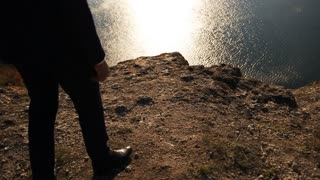 Close up of a man wearing elegant classical style walking on the hill of the mountain.
