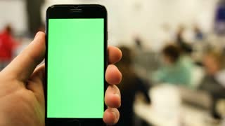 Close-Up of a Man's Hands Holding Green Screen Smartphone a. In the Background Bright Modern Office