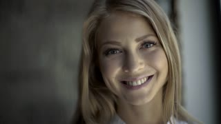 Close up Of A Smiling blond woman with natural makeup wearing white shirt