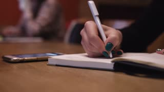 Close up of a Woman sitting and writing in her journal in busy coffee shop
