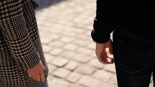 Close up of a young couple in love walking on the street tenderly holding hands.