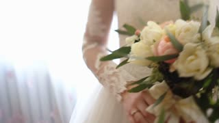 Close up of bride`s hands holding beautiful wedding bouquet of flowers of pink and white color.