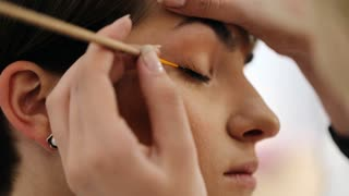 Close up of female arm of makeup artist holding eyeliner and applying it on eye of model with closed eyes