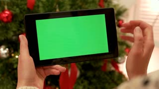 Close-up of female hands touching green screen on tablet Green screen Chroma Key. Close up. Tracking motion. Vertical. with blur christmas decoration background