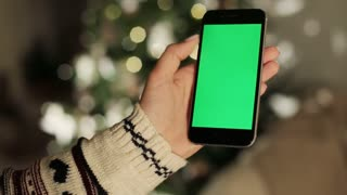 Close-up of female hands touching of smartphone. Green screen Chroma Key. Close up. Tracking motion. with blur christmas decoration background